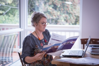 A carer reads through NDIS information at a table with an open laptop