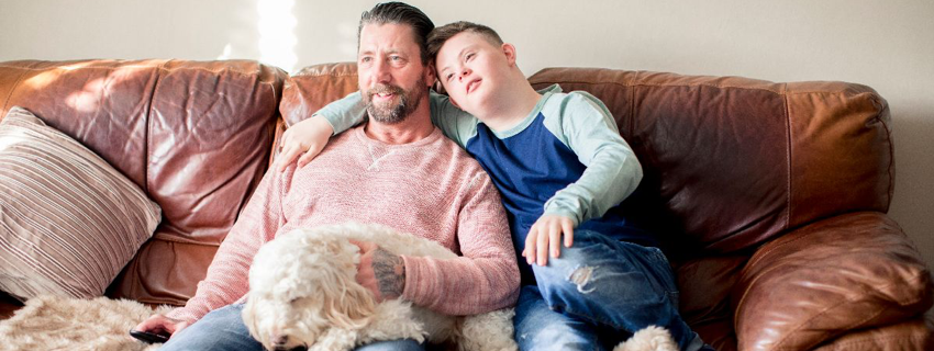 A boy and his carer sit on a couch with a dog