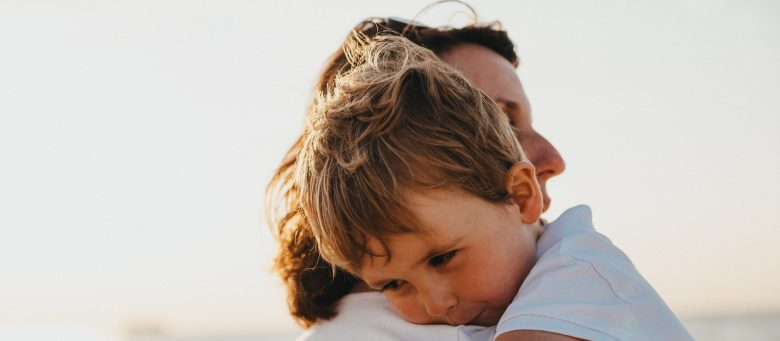 A young boy is held by his mother